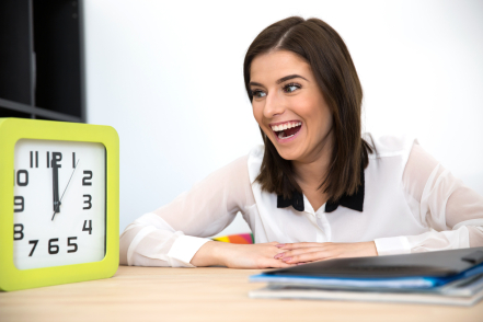 Surprised businesswoman sitting at the table and looking on the clock